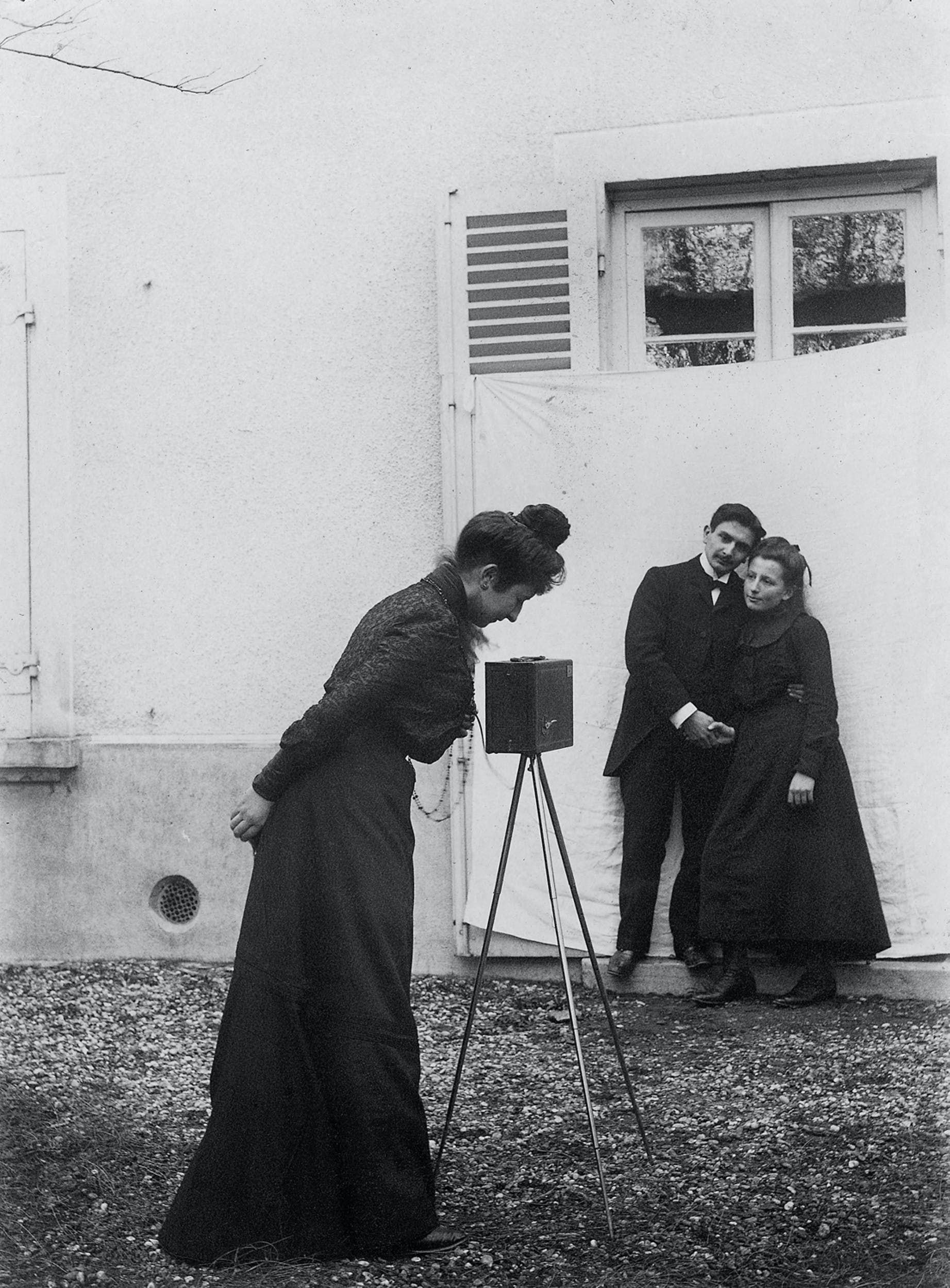 Autore non identificato Fotografa che guarda l'inquadratura, mentre ritrae una giovane coppia 1902 fotografia Collezione Favrod, Raccolte museali Fratelli Alinari, Firenze I Unidentified photographer  Woman photographing a young couple 1902 photograph Favrod Collection, Raccolte museali Fratelli Alinari, Florence