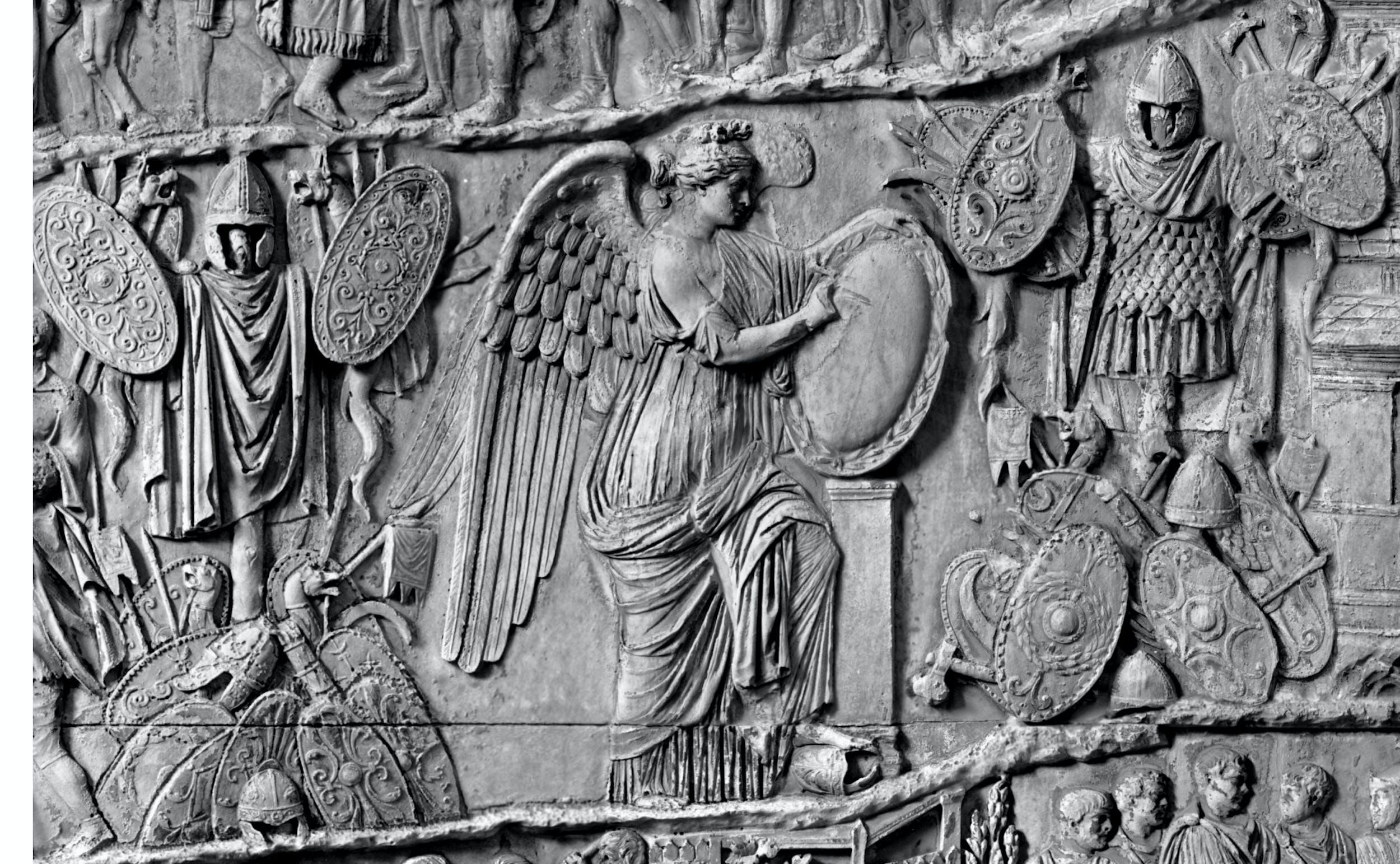 La Vittoria alata scrive sullo scudo le gesta di Traiano tra l'esposizione delle armi dacie conquistate durante la prima campagna